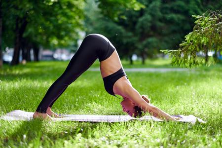 Yoga Downward Facing Dog Pose - Adho Mukha Svanasana Young woman practicing yoga meditation in nature at the park. Health lifestyle concept. Фото со стока