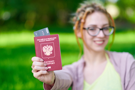 Portrait of happy tourist woman holding passport and coffee on holiday