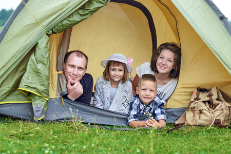 Family Parents and two children in camp tent. Happy Mother, father, son and daughter on Summer vacation.