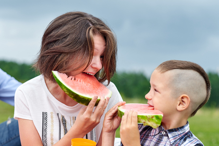 Mother and son eating watermelon in meadow or park. Happy family on picnic. outdoor portrait. Stock Photo