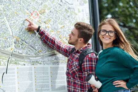 Young couple with a map in the city. Happy tourists sightseeing city with map. Banque d'images - 125340067