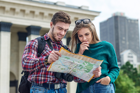 Young couple with a map in the city. Happy tourists sightseeing city with map. Banque d'images - 125340068