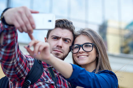 Happy couple of tourists taking selfie in showplace of city. Man and woman making photo on city background. Stock Photo