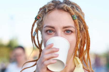 Portrait young woman with dreadlocks drinking coffee in paper cup