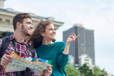 Young couple with a map in the city. Happy tourists sightseeing city with map. Stok Fotoğraf