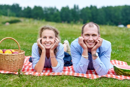 Young couple in love on picnic lying on tablecloth in red cell. Love couple resting in nature in meadow or park.