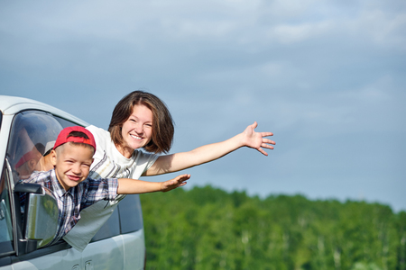 Happy young woman and her child looking out from windows. Family travelling by car.