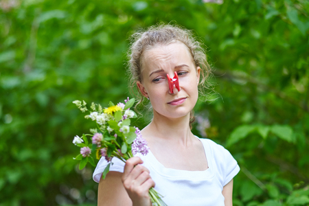 Allergy. Woman squeezed her nose with a clothespin, so as not to sneeze from the pollen of flowers.