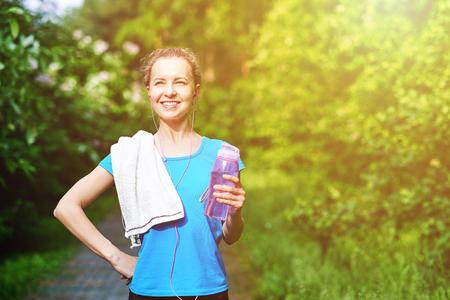 Fitness woman drinking water after running training in summer park. Reklamní fotografie - 125340147