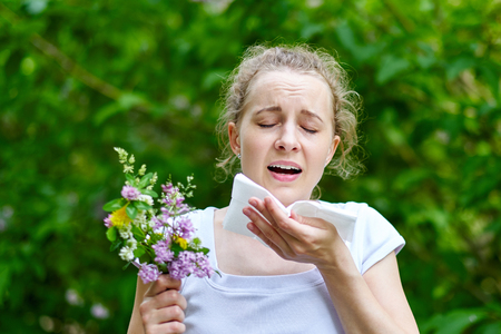 Young woman sneezing with bouquet of flowers. Concept: seasonal allergy Reklamní fotografie - 125340150