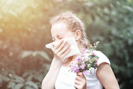 Pollen allergy, girl sneezing with bouquet of flowers. Concept: seasonal allergy. Reklamní fotografie - 125340152
