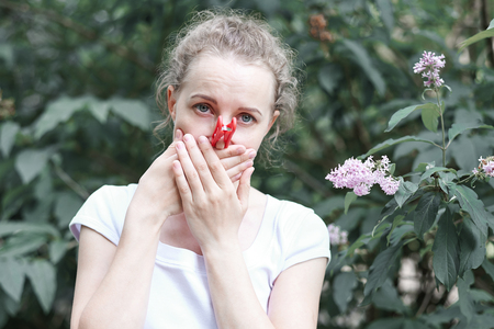 Allergy. Woman squeezed her nose with hand, so as not to sneeze from the pollen of flowers Reklamní fotografie - 125340154