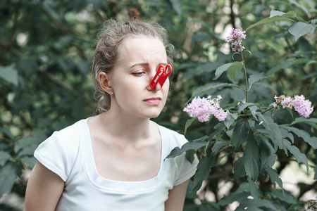 Allergy. Woman squeezed her nose with hand, so as not to sneeze from the pollen of flowers 스톡 콘텐츠