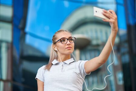 Businesswoman making selfies in front of office building. Smiling lady taking photos for her business partners abroad. Stock Photo