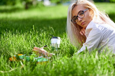 Happy blonde woman lying on grass, smiling and holding a cup of coffee on meadow. Stock Photo
