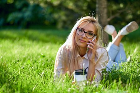 sexy blonde woman talking on the mobile phone and lying on meadow. Stock Photo