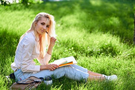 Young Blonde woman Student with a book, notebook and pen on meadow. Preparation from session and exams. outdoor portrait.