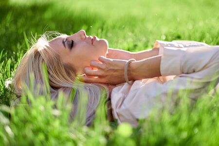 Woman listening music with her headphones and lying in meadow. Enjoys music, relaxes.