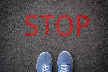 shoes standing before stop sign painted on asphalt, top view.