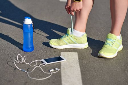 runner woman tying running shoes laces getting ready for race on run track stadium with bottle of water and smartphone