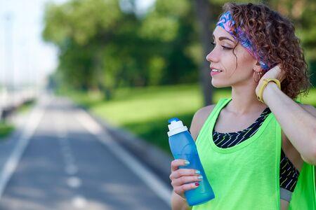 Running woman is having break, drinking water during run in summer park. Reklamní fotografie - 125340265