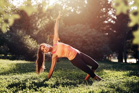 Yoga. Young woman practicing yoga or dancing or stretching in nature at park. Health lifestyle concept.