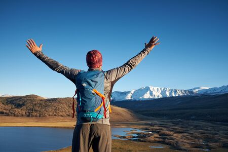 Hiker with backpack standing on top of a mountain with raised hands and enjoying sunrise Stock Photo