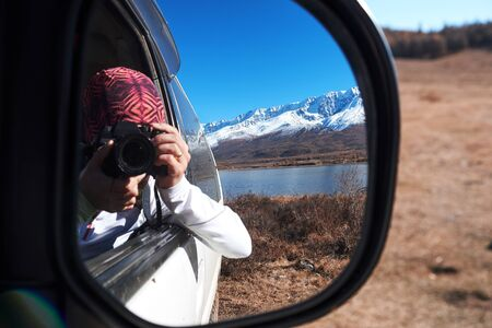 Reflection of a photographer woman with a camera in the rear view mirror of a car in nature mountain. Stock Photo