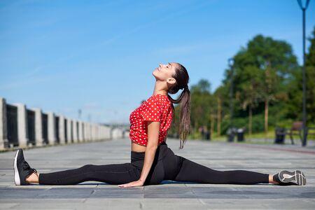Stretching gymnast woman doing split, twine in city. Reklamní fotografie - 125340385