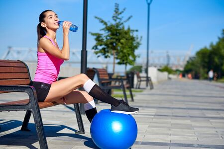 Fitness woman with bottle and rubber fit ball. Female drinking water after training on bench in summer park.