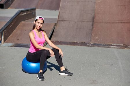 Fitness woman doing stretching exercises with fit ball on urban city background