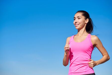 Running fitness woman. Training woman in pink top on a blue background.
