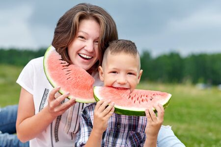 Mother and son eating watermelon in meadow or park. Happy family on picnic. outdoor portrait. Standard-Bild - 129167193