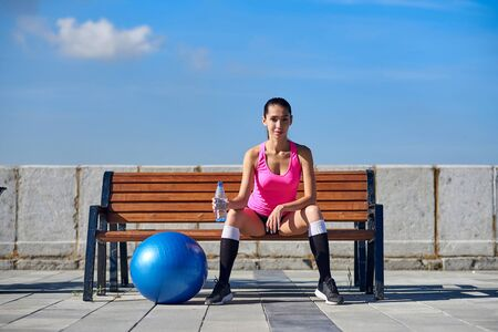 Fitness woman with bottle and rubber fit ball. Female drinking water after training on bench in urban city.