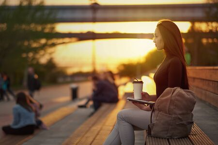 Young asian woman with coffee and book in the evening at sunset. outdoor city portrait. Stockfoto
