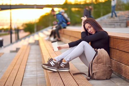 Young asian woman teen with coffee. outdoor city portrait.