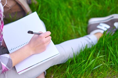 teenage girl student writing in notebook in park. Preparation for exams at college or university. Zdjęcie Seryjne