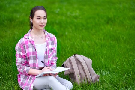 Young Asian woman writing in notebook seated on grass in green summer park.