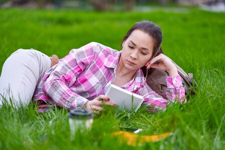 Young Asian woman reading book lying on grass in green summer park