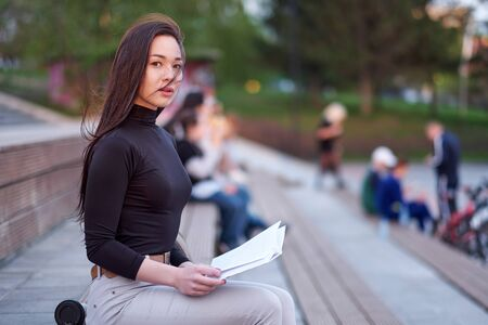 Young Asian woman student reads a lecture book. Preparation from the session and exams. outdoor city portrait. Stockfoto