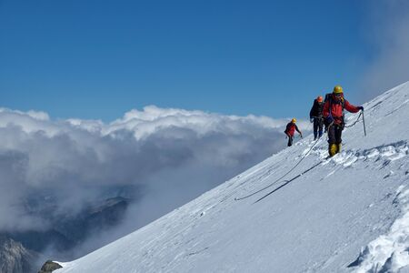 Bunch of mountaineers climbs to the top of a snow-capped mountain
