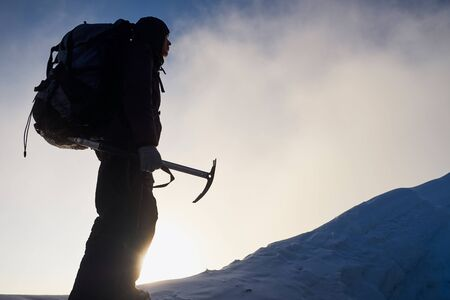 Silhouette of alpinist man going to the top of mountain at sunrise.