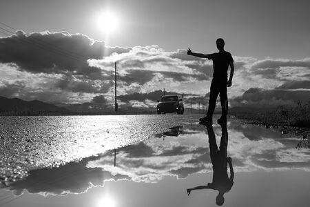Travel man hitchhiking. Reflection in a puddle. Silhouette of man with a raised hand thumb up.