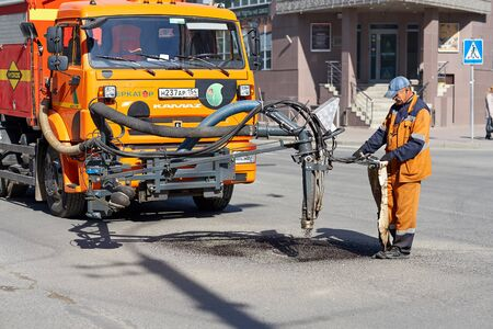 NOVOSIBIRSK, Russia - September 2, 2019: Workers on a road construction, industry and teamwork. People working on an asphalt road with shovels
