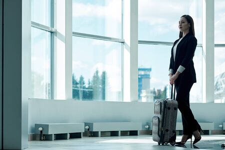 Young asian business woman at the airport with trolley bag, waiting for departure. Stock fotó