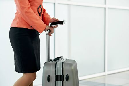 Young business woman in airport with baggage trolley bag and smartphone
