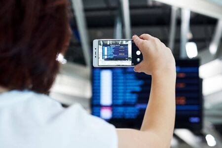 Hand takes photo on smartphone in airport. On the screen, the flight departure schedule.