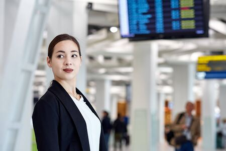Young asian business woman at the airport with trolley bag, waiting for departure. Stock Photo