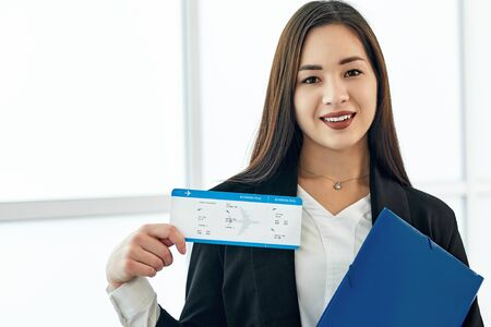 Asian Business woman with tickets waiting for departure in airport.