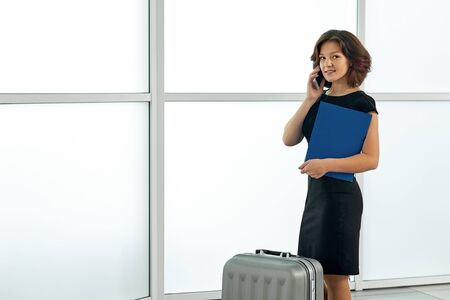 Young woman at the airport with trolley bag, talking on the phone and smiling. Stock Photo